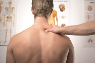 男性が肩を揉んでもらっている写真