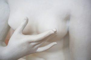 女性の胸部の石膏像、左胸に手を添えている写真