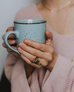 女性がマグカップを包むように持っている写真