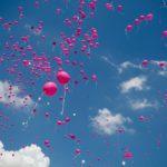 ピンクの風船が空一面に上がっている画像