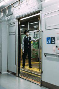 電車に乗っているマスクをした駅員の画像
