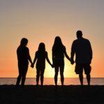 夕日を背に4人が手を繋いだ写真