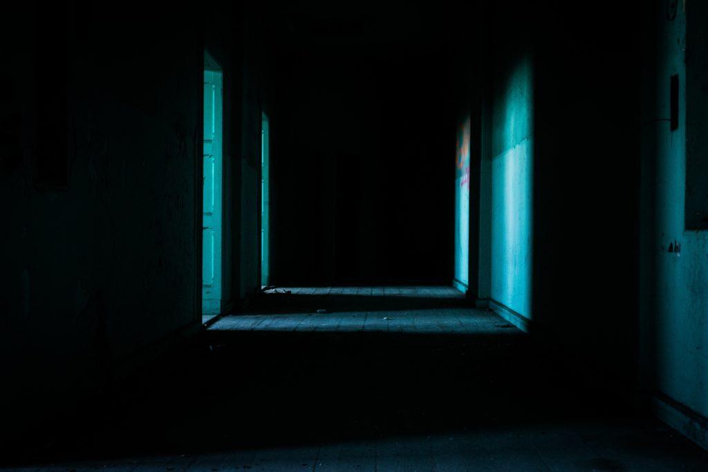 暗い廊下に開いたドアから部屋の光が差し込んでいる夜の写真