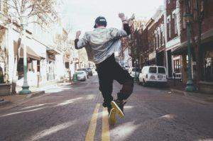 道路で飛び跳ねてガッツポーズをしている男性の写真
