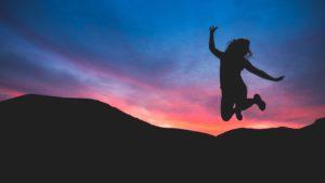 朝焼けをバックにジャンプしている女性の写真