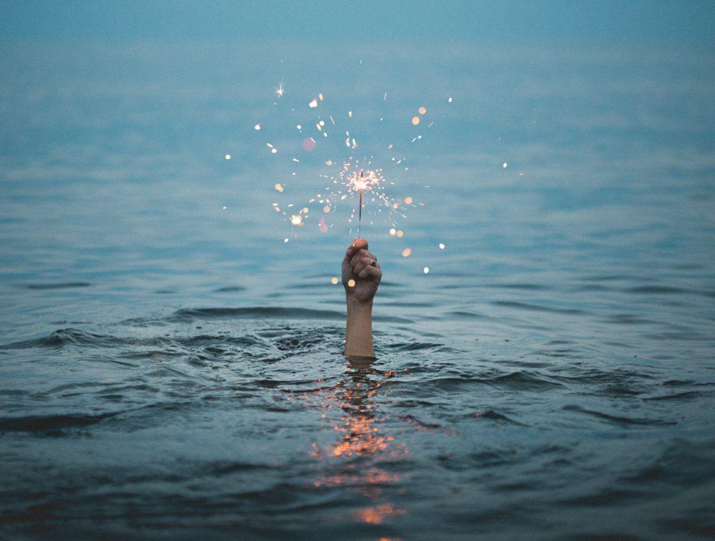 水から突き出た腕が花火を持っている写真