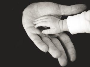 大人の手に赤ちゃんの手が乗せられている写真