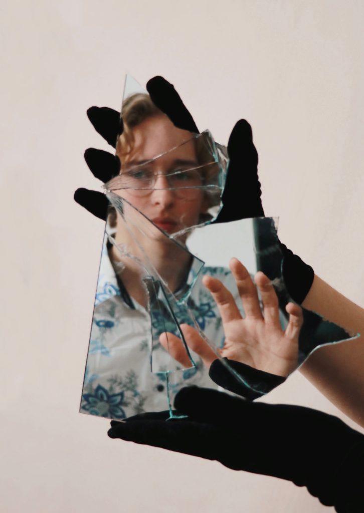 黒い手袋をして持った割れた鏡にメガネの女性が写っている写真