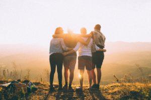 4人の男女が朝日に向かって肩を組んでいる写真