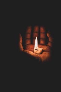 手のひらの上で小さい蝋燭が燃えている写真