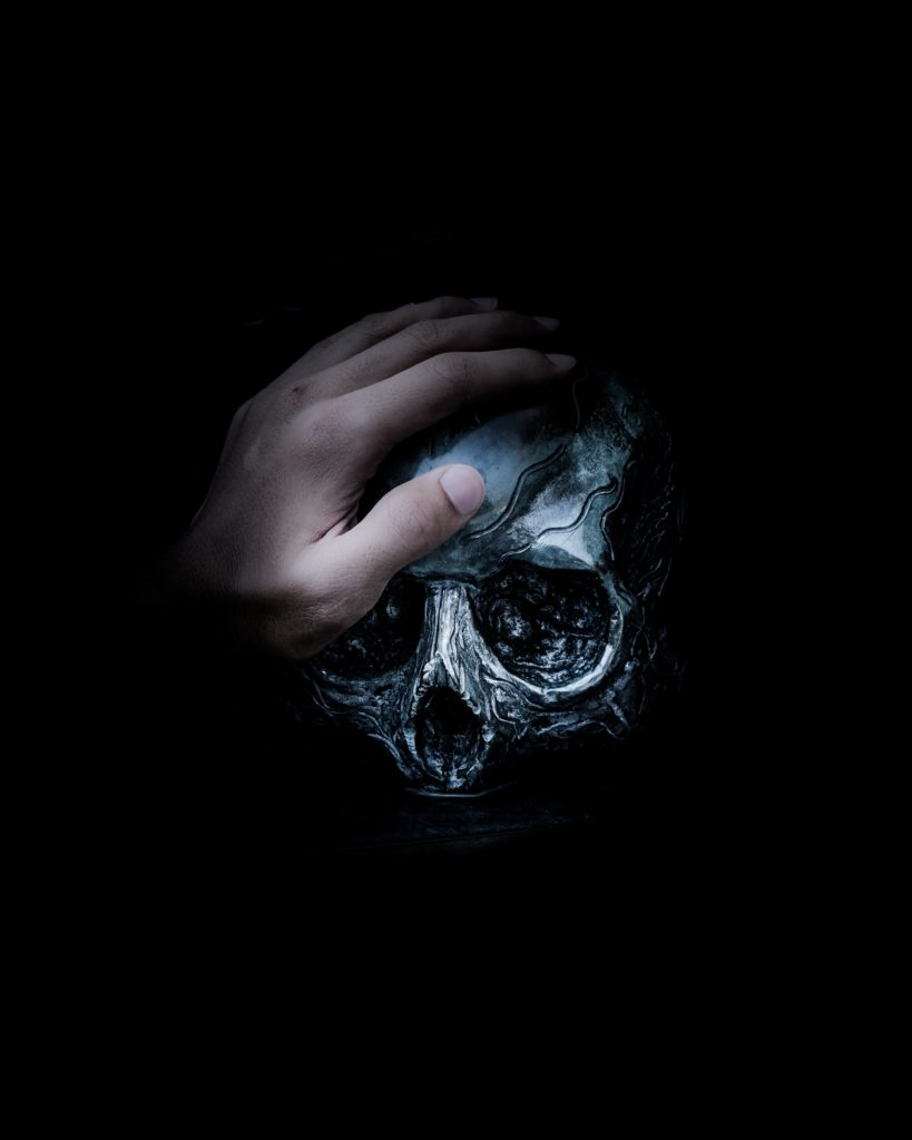 骸骨の頭に手をのせた写真