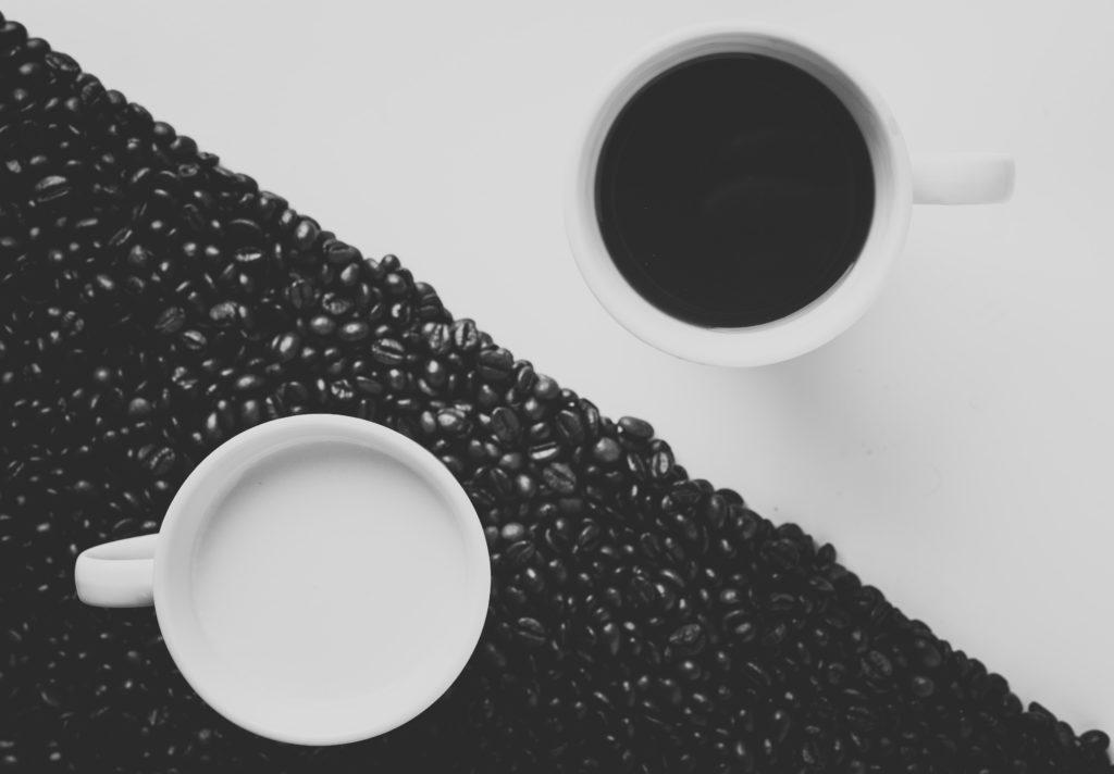 白地にコーヒーが注がれたカップと黒地にミルクが注がれたカップの写真