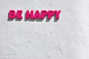 白壁にピンクの文字でBE HAPPYと書かれている写真