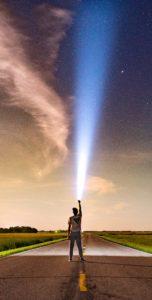 拳を突き上げている人に光が降り注いでいる写真