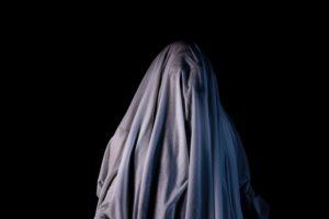 暗闇で白い布をかぶってお化けのふりをしている人の写真