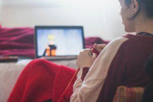 女性が膝にブランケットをかけてタブレットでナルトを見ている写真