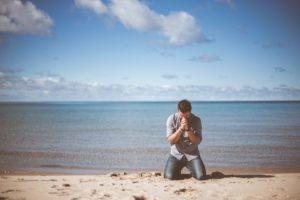 海をバックに砂浜で祈る男性