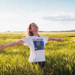 草原で女性が青空に向かって両手を広げている写真
