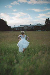 白いドレスを着て逃げる女性の後ろ姿の写真