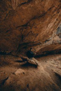 岩の洞窟みたいな場所で1人物思いに耽る男性の写真