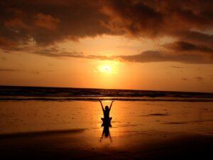 朝日に向かって手を広げて瞑想する人の写真