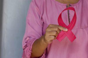 ピンクの手術着を着てピンクリボンを持っている写真