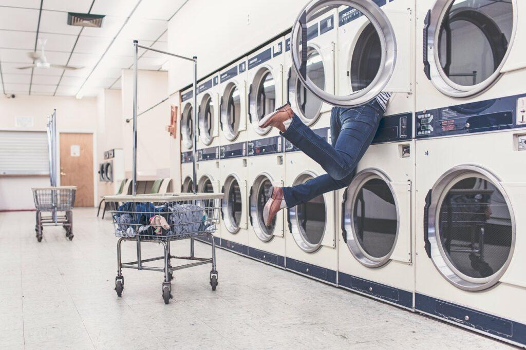 コインランドリーの乾燥機に上半身を突っ込んだ人の写真