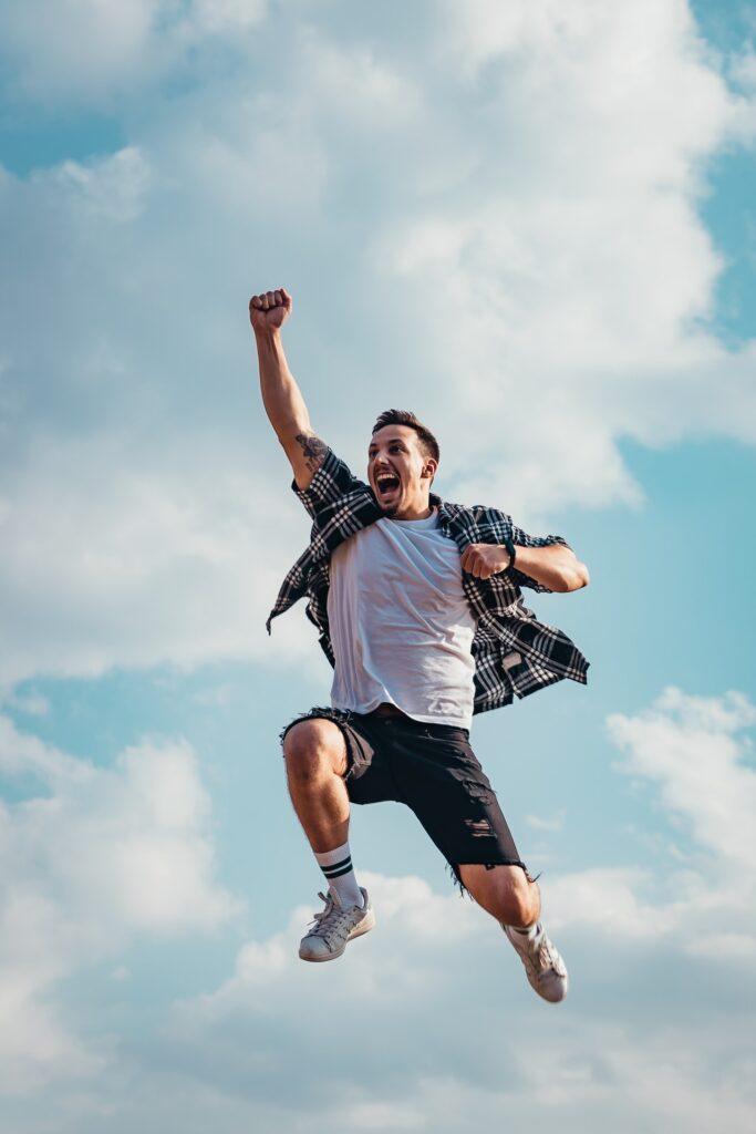 空に拳を突き上げて楽しそうにジャンプする男性の写真