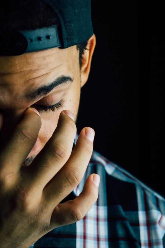 目頭を押さえている男性の写真