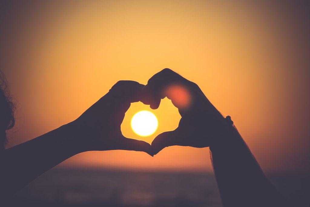 手で作ったハートの中の夕日の写真