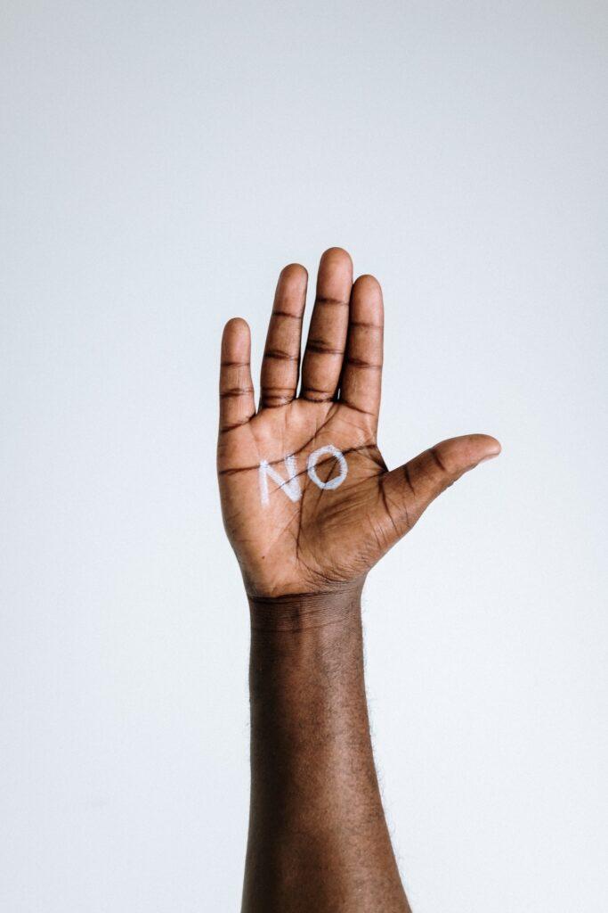 黒人の掌に白いペンでNOと書かれた写真