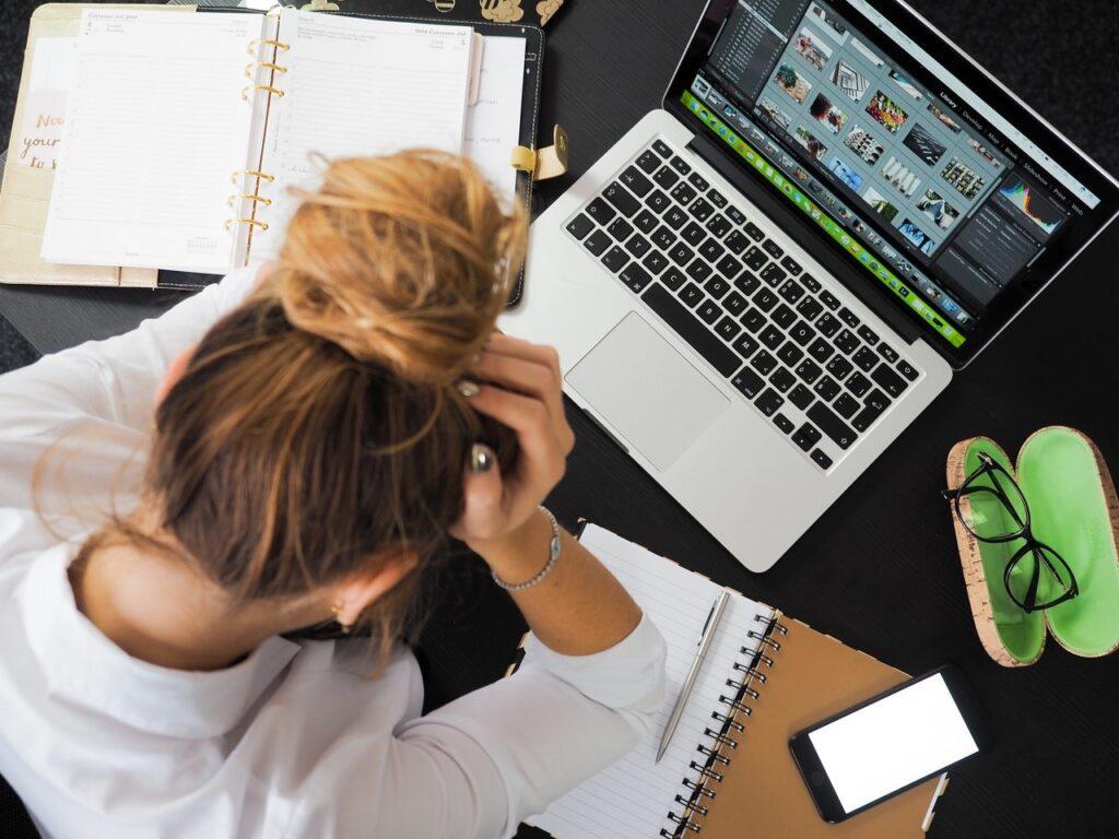 パソコンとノートを広げて頭を抱えた女性の写真