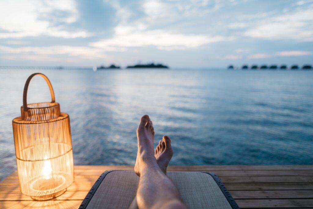 海を見ながら裸足で寝そべる男性の足