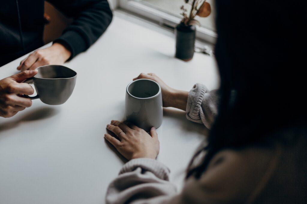 2人の人が向かい合ってコーヒーを飲んでいる様子