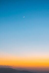 まだ月が残っている空に太陽が登り始めて朝焼けしている