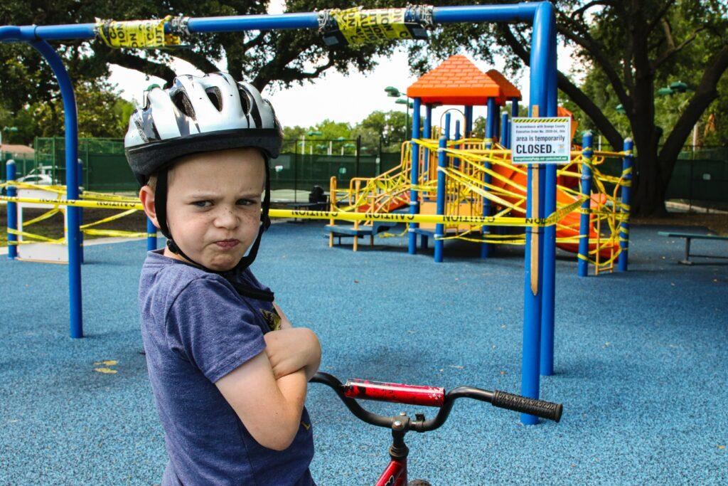 自転車から降りて、ヘルメットを被った少年が起こった顔で腕組みしてこちらを見ている