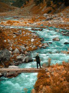 橋の上で男性が川の流れを眺めている