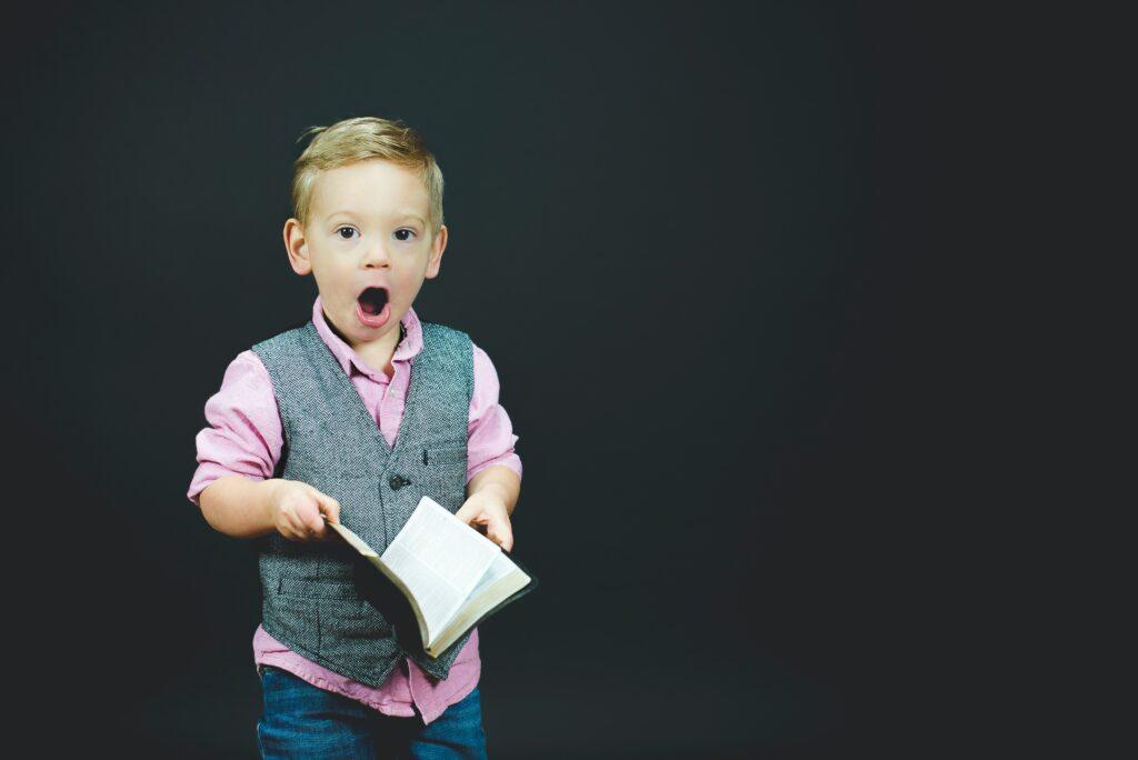 男の子が開いた本を持って、びっくりした顔でこちらを見ている