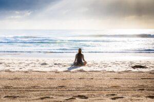海辺で海を見ながらあぐらで座っている女性